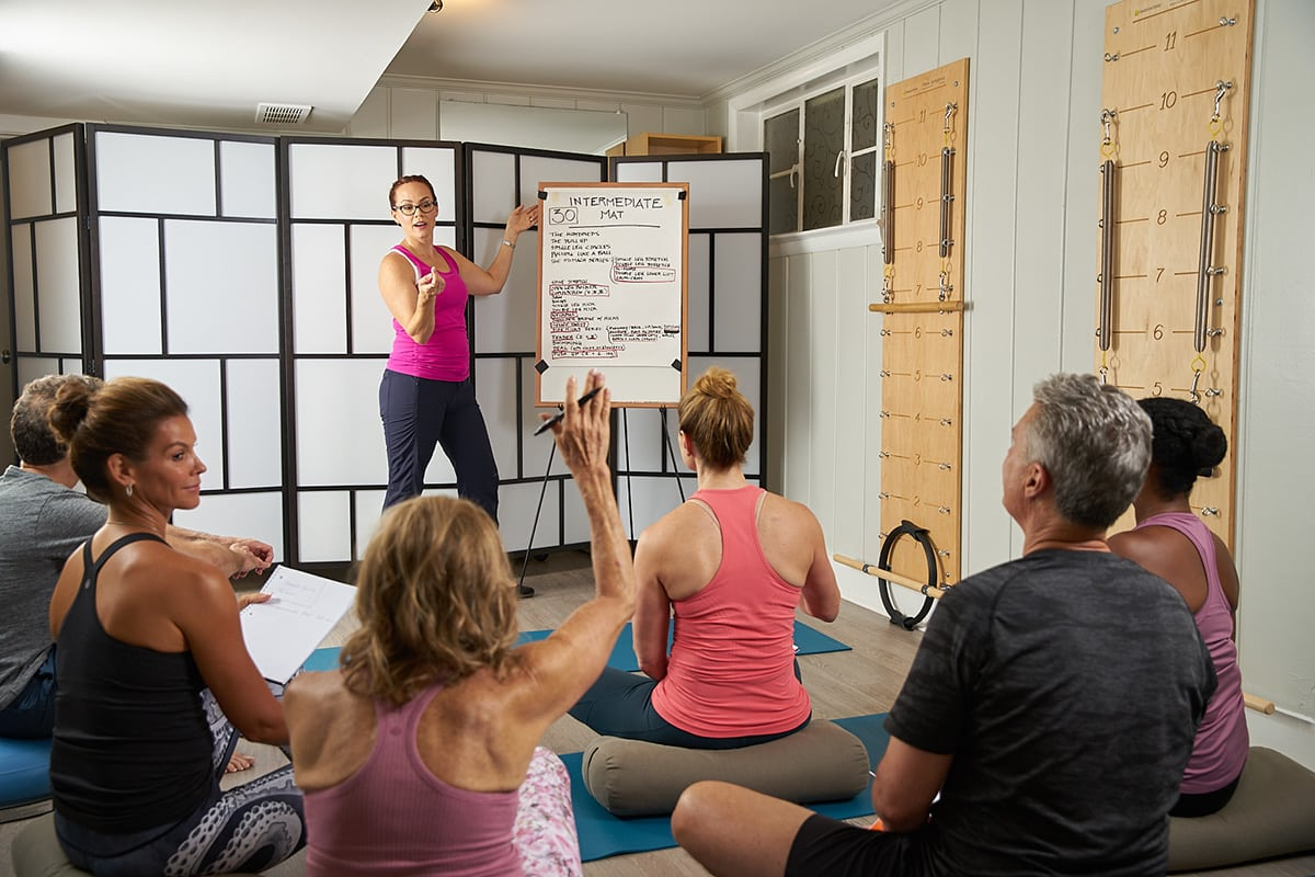 Instructor presenting during a comprehensive Pilates teacher training program